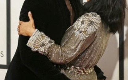 Kanye West grabs Kim's butt as he embraces her at the Grammys red carpet
