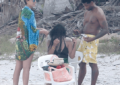 Usher pictured helping his wife take out her hair extensions on the beach
